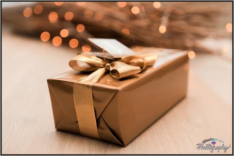 Een mooie doosje in goudkleur erachter een kerstverlichting