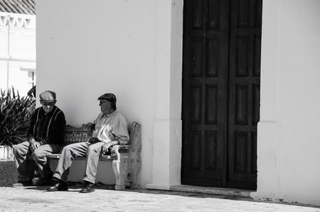 bijpraten - Deze 2 mannen bespreken hun dag voor een kerkje in Armacao de Pera. Hoe onopvallend ik ook probeerde te zijn...mijn camera viel de linker wel op. - foto door aschuijffel op 31-05-2013 - deze foto bevat: kerkje, portugal, algarve, zwart wit, oude mannen