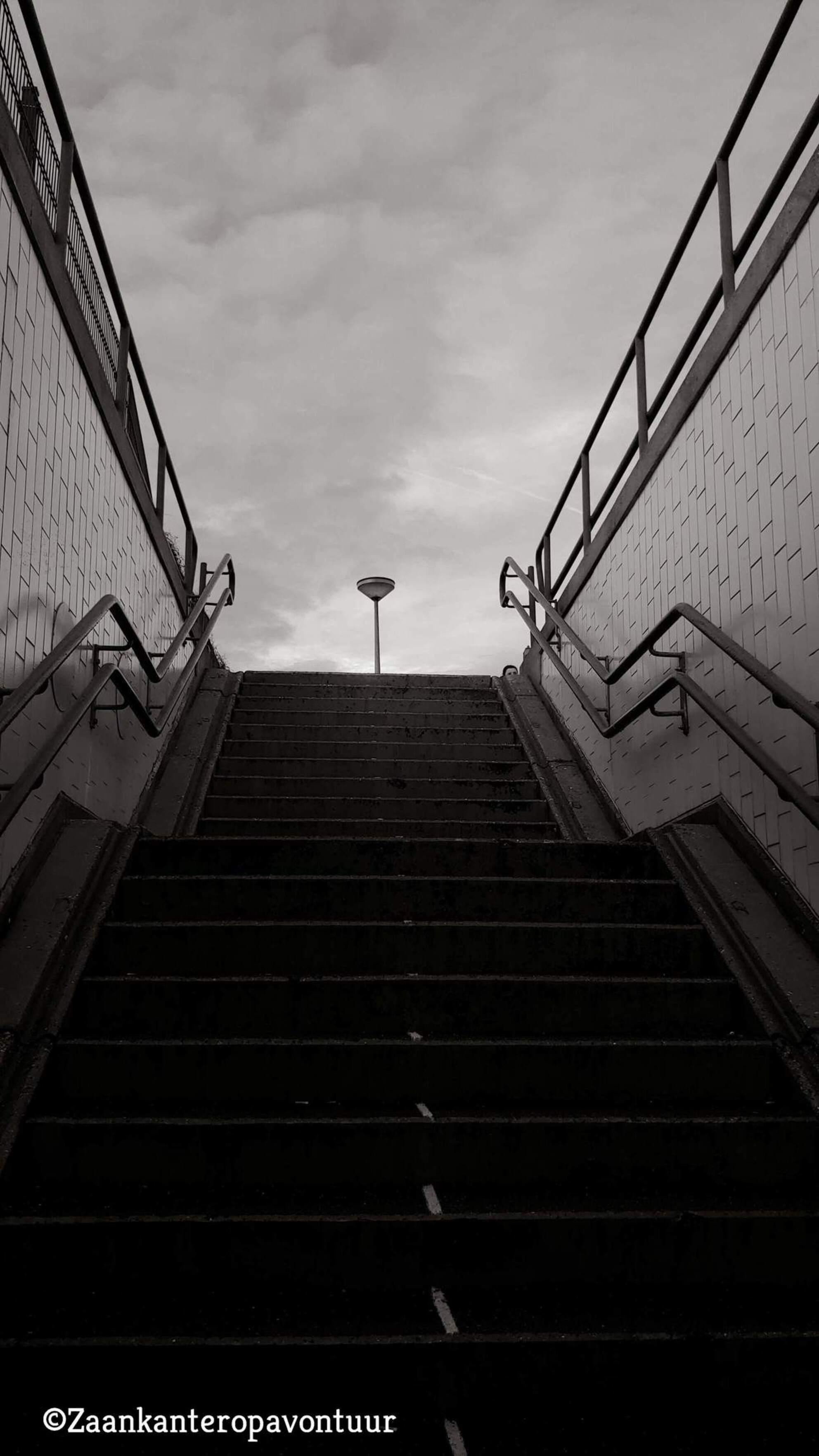 Zaankanteropavontuur - Lopend door een fietstunneltje zag ik dit stilleven. Natuurlijk staat deze lantaarn niet in het midden maar ik vond m zo wel mooi doorlopen met de st - foto door Zaankanteropavontuur op 11-12-2018 - deze foto bevat: wolken, straat, trap, spiegeling, urban, zwartwit, lantaarnpaal, fietstunnel