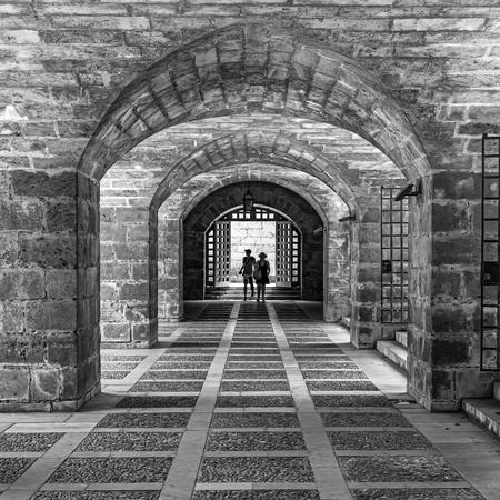 tunnel vision - toegang tot de catedral de mallorca in palma - foto door Aaddevogel op 10-04-2021 - locatie: Nord de Palma District, Balearic Islands, Spanje - deze foto bevat: zwart wit, palma, mallorca, tunnel, architectuur, spanje, straat fotografie, infrastructuur, staand, zwart en wit, stijl, lijn, metselwerk, symmetrie, oriëntatiepunt, steen, facade