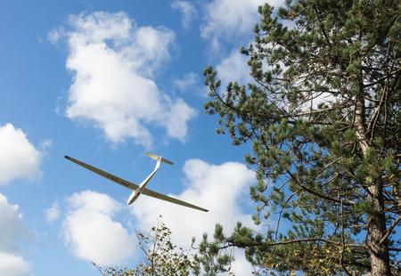 Flying Low - Het vliegtuigje vloog rakelings langs het boom tijdens inzet van de landing. Ik had het geluk om het optijd in beeld te krijgen.  Het is even wennen  - foto door Lilian2010 op 10-04-2021 - deze foto bevat: vliegtuig, heemskerk, lucht, wolken, zweefvliegtuig, nh duinreservaat, wolk, lucht, meubilair, fabriek, vliegtuigen, stoel, glijden, boom, vliegtuig, cumulus