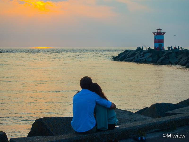 Together - Tijdens een fotografische wandeling om de Olympus E-PL3 te testen (tov mijn 5dII) zag ik dit stel zitten, vermoedelijk wachtend op de zonsondergang. - foto door mkview op 03-08-2014 - deze foto bevat: man, vrouw, wolken, zon, zee, water, vuurtoren, sunset, zonsondergang, liefde, tegenlicht, scheveningen, haven, stenen, stel, rotsen, verliefd, havenhoofd, noordzee, bewolking, omarmen