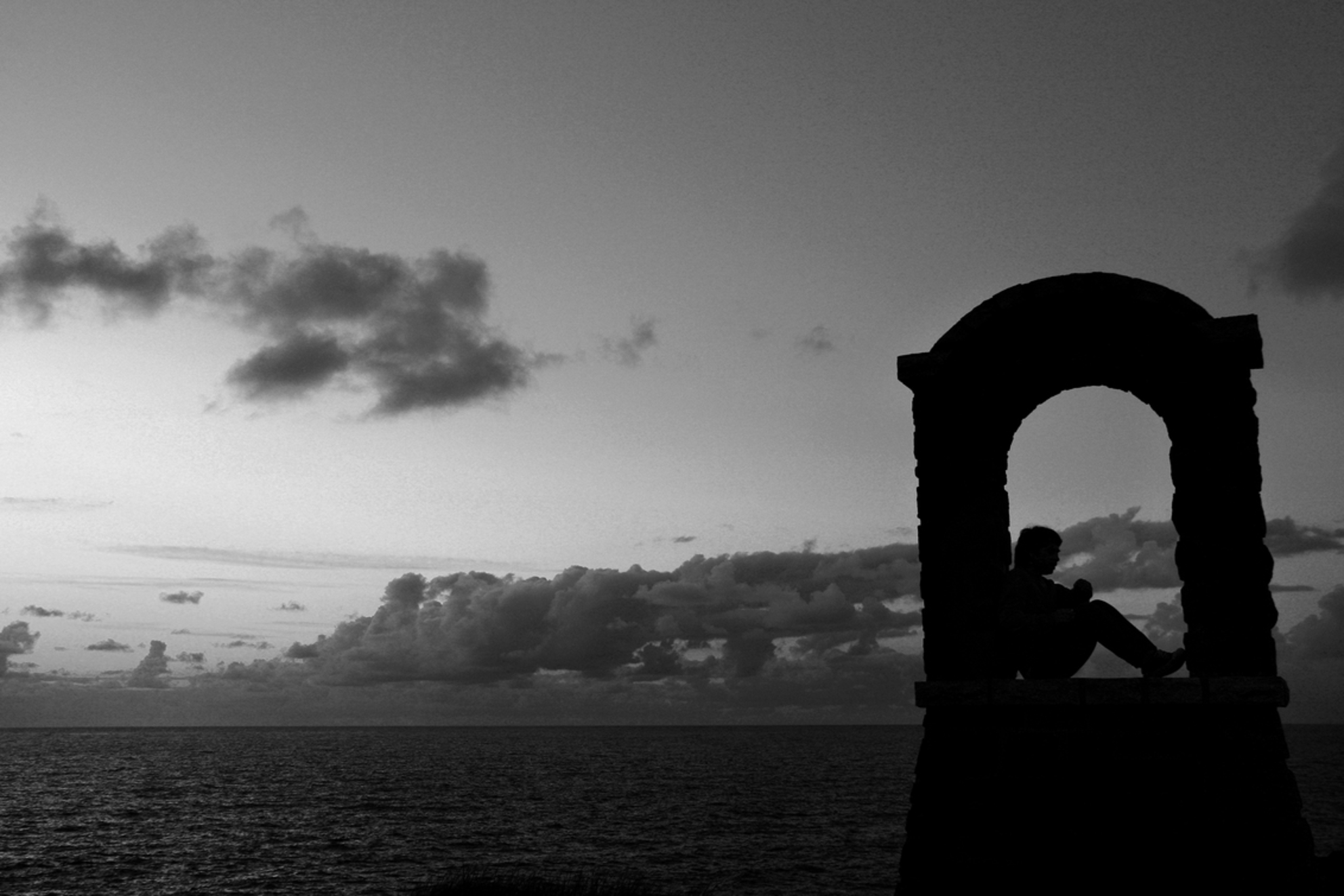 De gedachte - Tijdens zonsondergang liep ik voorbij een kleine poort met een jongen in gedachten verzonken. - foto door mennovermeulen op 09-05-2010 - deze foto bevat: wolken, zon, zee, zonsondergang, silhouet, poort, denken, menno vermeulen