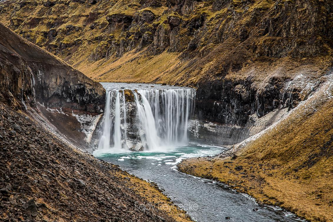 DALFOSS - Na een mooie wandeling door een kloof kwamen we uiteindelijk uit bij deze prachtige waterval.   Dalfoss - Vatnsdalsa IJsland - foto door eddy-reynecke op 19-03-2019 - deze foto bevat: water, natuur, licht, herfst, sneeuw, vakantie, ijs, landschap, tegenlicht, ijsland, bergen, rivier, iceland, lange sluitertijd, dalfoss
