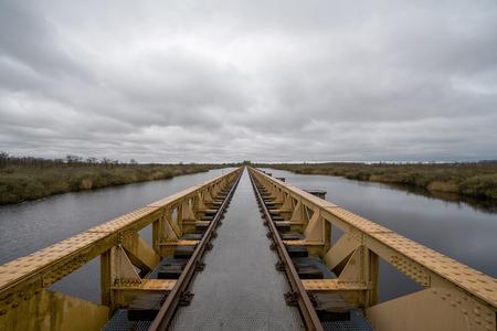 Moerputtenbrug - Moerputtenbrug In 1890 werd de Langstraatspoorlijn 's-Hertogenbosch-Lage Zwaluwe in gebruik genomen. Het spoor liep door het natte laagveengebied van - foto door stevendijk3 op 15-04-2021 - locatie: 's-Hertogenbosch, Nederland - deze foto bevat: moerputtenbrug, brug, geel, water, lucht, wolk, fabriek, watervoorraden, natuur, hout, boot, natuurlijk landschap, meer