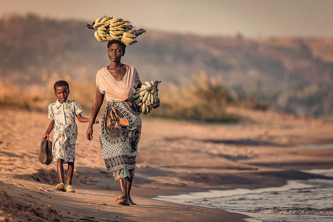 Bananas - Vrouw en kind met bananen op het hoofd - foto door EdPeetersPhotography op 04-03-2020 - deze foto bevat: vrouw, mensen, water, zonsondergang, kind, bananen, afrika, wandelen, cultuur, reisfotografie, malawi, malawimeer
