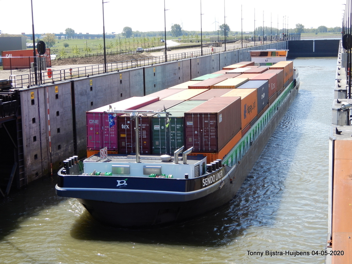 schutten - dit is het schip dat op de foto van gisteren de 3e kolk invoer vanaf de Lek, het schutten ging vrij snel omdat de waterstand laag was en er dus geen  - foto door Tonny1946 op 06-05-2020 - deze foto bevat: groen, rood, wit, water, oranje, zwart, bomen, sluis, schip, kade, beatrix, nieuwegein, containers, lantaarnpalen