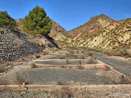 Steenzout droog bekkens - Hier zie je de oude bekkens waar het zoutwater  uit de rivier in ging om in de zon te drogen waarna het steenzout achterbleef. Het water in de rivier - foto door ocelot_zoom op 08-10-2020 - deze foto bevat: natuur, landschap, bomen, bergen, spanje, nicojo, steenzout