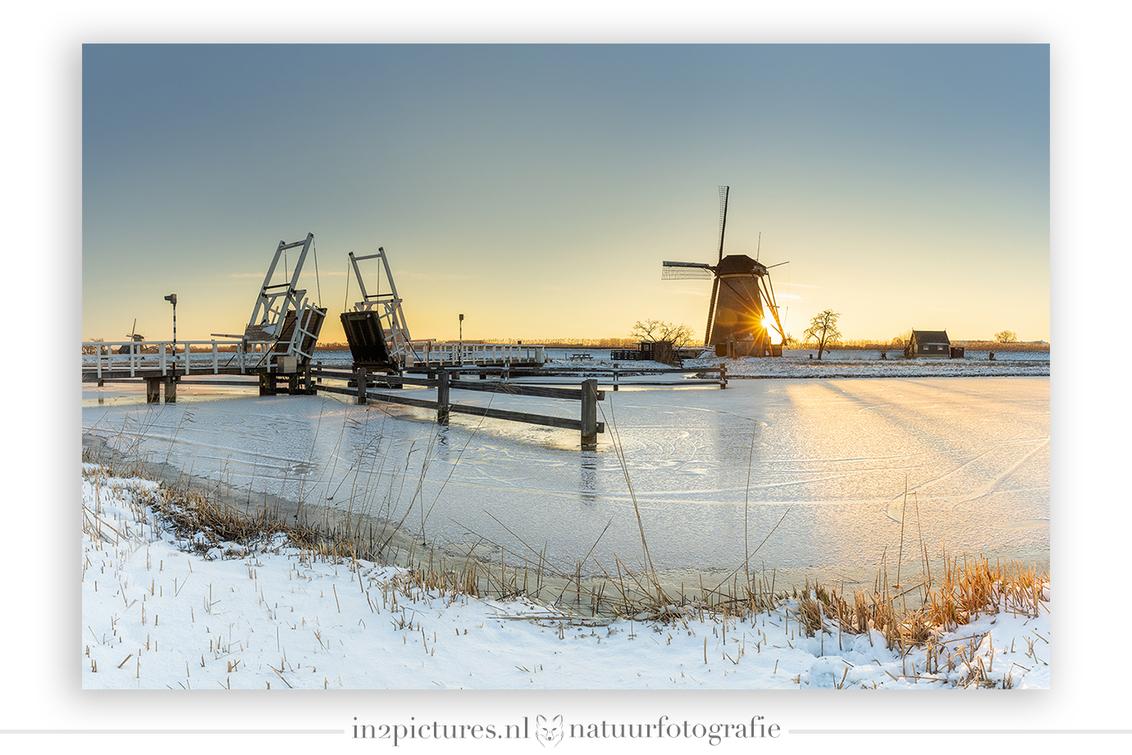 Hollandse winter - Zo, de ijsperiode is voorbij, nu is het tijd om de foto's allemaal eens door te spitten. Dit plaatje is voor mij toch wel het ultieme Holland gevoel. - foto door in2picturesnature op 15-02-2021 - deze foto bevat: zon, water, panorama, natuur, licht, sneeuw, winter, zonsondergang, ijs, landschap, brug, molen, holland, ophaalbrug