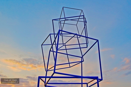 Fietsbrug kunstwerk Schinveld - Fietsbrug kunstwerk Schinveld bij zonsondergang. - foto door cockie op 15-04-2021 - locatie: 6451 Schinveld, Nederland - deze foto bevat: zonsondergang, kunstwerk, blauw, kubus, vierkant, brug, fietsbrug, lucht, wolk, driehoek, elektriciteit, parallel, kunst, elektrisch blauw, symmetrie, elektrische voeding, bovengrondse hoogspanningslijn