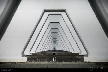 Dwars door de Zeelandbrug - Aan de zuidkant van de Zeelandbrug de dijk over geklommen en recht onder de brug afgedaald tot iets boven het water: het punt waar je dwars door peil - foto door framefotografie op 27-08-2018 - deze foto bevat: abstract, lijnen, architectuur, brug, zeeland, perspectief, zeelandbrug
