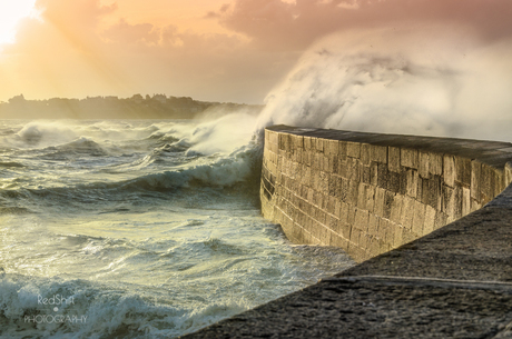 Big waves crushing on stone pier