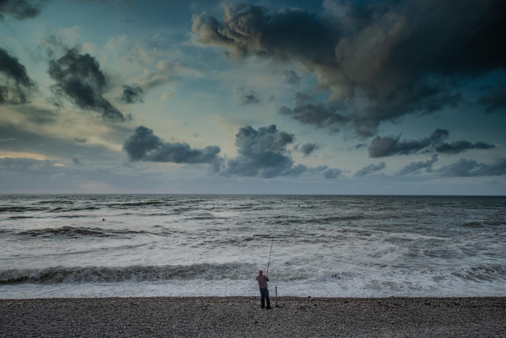 De visser - Eenzame visser op het strand van Etretat - foto door TaraKiekt op 09-08-2019 - deze foto bevat: wolken, zon, strand, zee, water, natuur, licht, zonsondergang, vakantie, spiegeling, vissen, landschap, tegenlicht, zand, haven, kust, visser, oceaan, kliffen - Deze foto mag gebruikt worden in een Zoom.nl publicatie