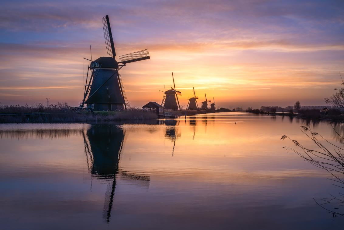Sunrise at Kinderdijk - Bijna windstil en wat wolken. Combineer dat met het UNESCO Werelderfgoed van Kinderdijk en je hebt alle ingrediënten voor een geweldige foto. - foto door SiebringPhotoArt op 26-02-2021 - deze foto bevat: wolken, zon, water, natuur, geel, landschap, tegenlicht, voorjaar, molen