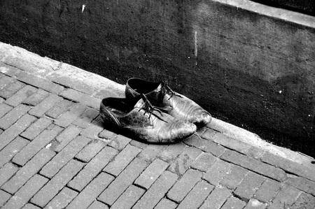 left shoes in amsterdam - wat zwervend door de Amsterdamse steegjes kwam ik dit paar tegen, het leek me nogal raar dat ze daar zo achtergelaten waren, maar de verweerde schoen - foto door moetsj op 29-05-2016 - deze foto bevat: oud, mensen, amsterdam, straat, wit, zwart, schaduw, schoenen, straatfotografie, verval, monochrome, Black and white