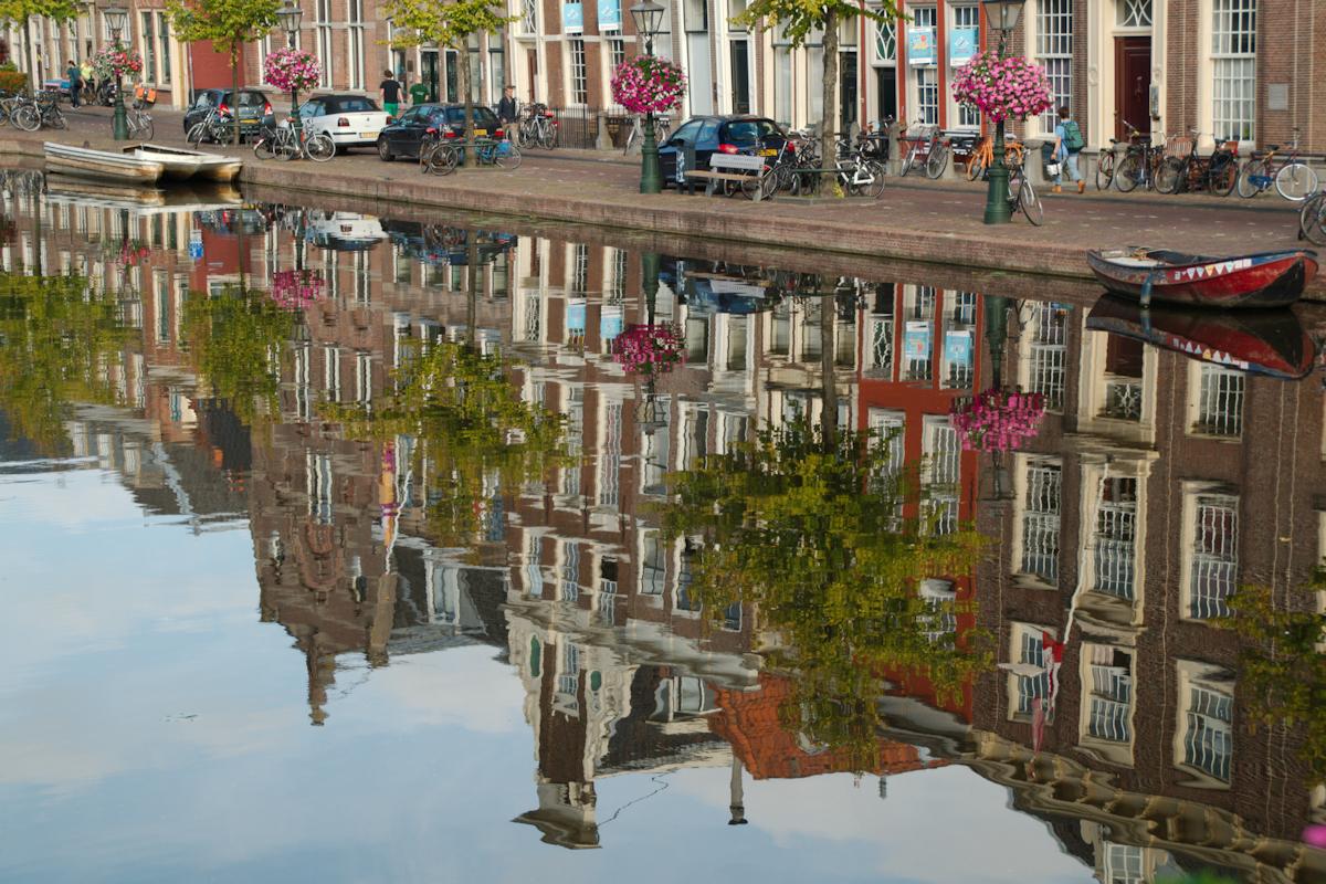 Gracht - Spiegeling - foto door Erik-54 op 13-04-2021 - locatie: Leiden, Nederland - deze foto bevat: stadslandschap, gracht, stad, water, zomer, spiegeling, water, fabriek, gebouw, dag, voertuig, venster, boom, wiel, lichaam van water, waterscooters