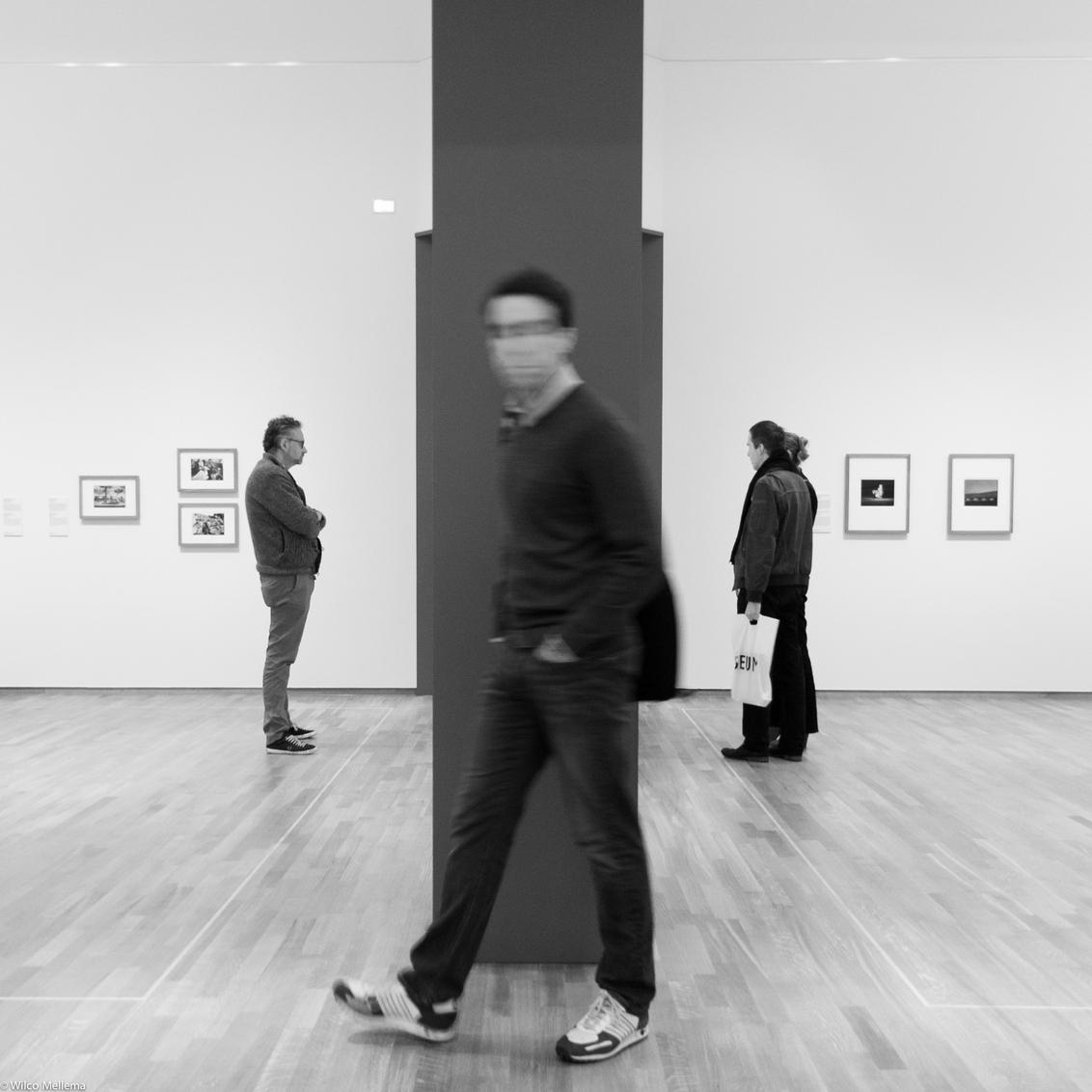 Tussen twee ruimten - Een man loopt in het Rijksmuseum tijdens de fototentoonstelling Modern Times tussen twee expositieruimten door. - foto door wilcofm op 30-05-2015 - deze foto bevat: man, mensen, portret, jongen, zwartwit, 50mm