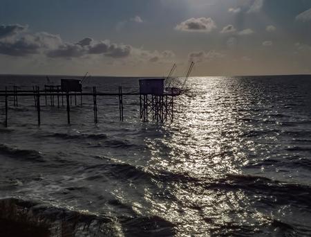 Cabanes (vissershutten) - Met al dat thuiszitten ga je nog eens in de oude doos kijken. Deze foto maakte ik nog met mjn votrige camera, de Fuji HS-10. in Frankrijk, aan de Atl - foto door PeterKosterHT op 17-01-2021 - deze foto bevat: lucht, wolken, zon, zee, water, panorama, natuur, licht, avond, zonsondergang, vakantie, spiegeling, landschap, tegenlicht, kust, visserij, vissers, vissershuisjes, oceaan, zonneharp, franrijk, charente, Atlantische Oceaan, vissershut, charente-maritime, vissershutten, cabanes