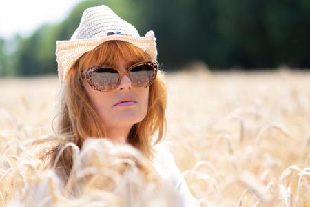 Magic Summer - model : Silvia - foto door Gans op 25-07-2018 - deze foto bevat: vrouw, zon, licht, graan, reflectie, zomer, goud, fashion, zonnebril, zomers, hoedje, redhead, hans van den broek