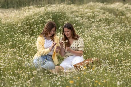 Vriendinnen zittend in zomers wilde bloemen veldje