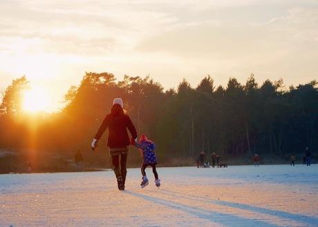 Meisje leert adhv haar moeder schaatsen op natuurijs