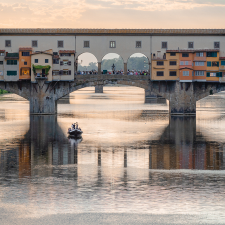 """Bridge Ponte del Vecchio in Florence - Bridge Ponte del Vecchio (""""Old Bridge"""") over Arno river, boat under the bridge, Florence, Italy, Tuscany - foto door samards op 21-05-2019 - deze foto bevat: old, bridge, water, sun, reflection, yellow, monument, skyline, art, light, boat, travel, landscape, florence, river, city, reflections, vecchio, view, summer, sky, italian, window, place, italy, architecture, firenze, landmark, day, sunny, tuscany, tourist, history, ancient, colorful, scene, arno, location, europe, european, famous, medieval, attraction, vacation, Sightseeing, destinations, picturesque"""