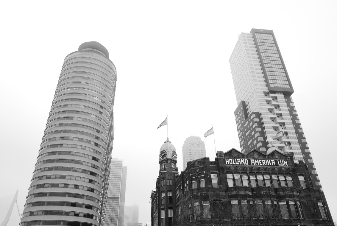 Rotterdam - Hotel New York - Zicht op hotel New York, iconisch gebouw van Rotterdam (links nog de Erasmusbrug zichtbaar). - foto door Krulkoos op 08-01-2020 - deze foto bevat: rotterdam, architectuur, mist, mistig, gebouw, stad, erasmusbrug, toren, stadsgezicht, zwartwit, flat, modern, wolkenkrabber, hoogbouw, New York, hotel new york, oud gebouw, Holland Amerika lijn, maurice weststrate, lx100, wolkekrabber