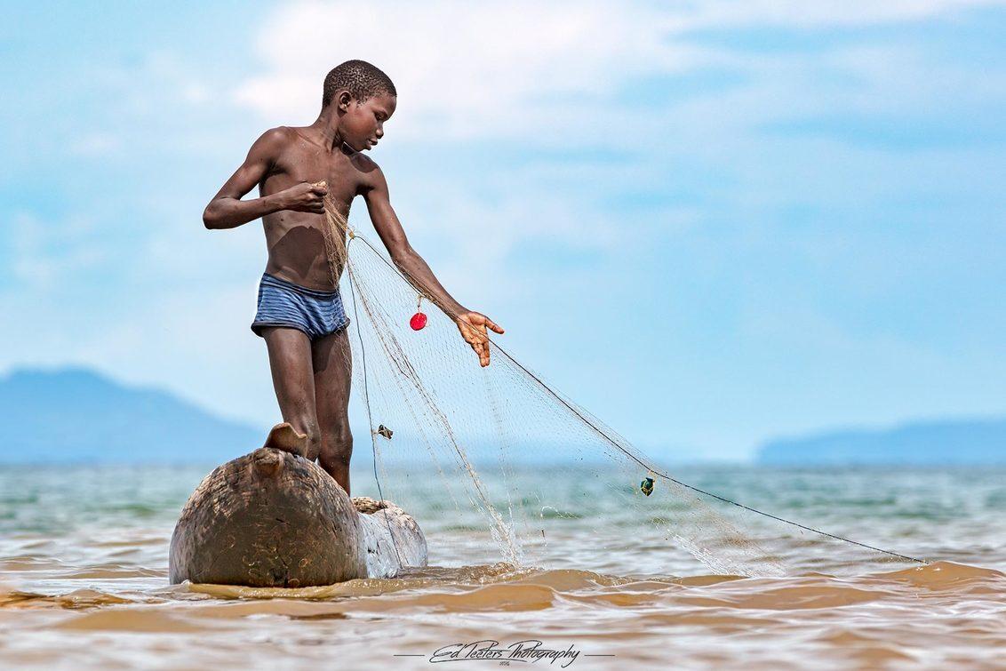 Fishing with a net - Jongen vissend op een boot op Lake Malawi - foto door EdPeetersPhotography op 27-12-2020 - deze foto bevat: water, natuur, portret, vissen, jongen, afrika, straatfotografie, reisfotografie, malawi, edpeetersphotography