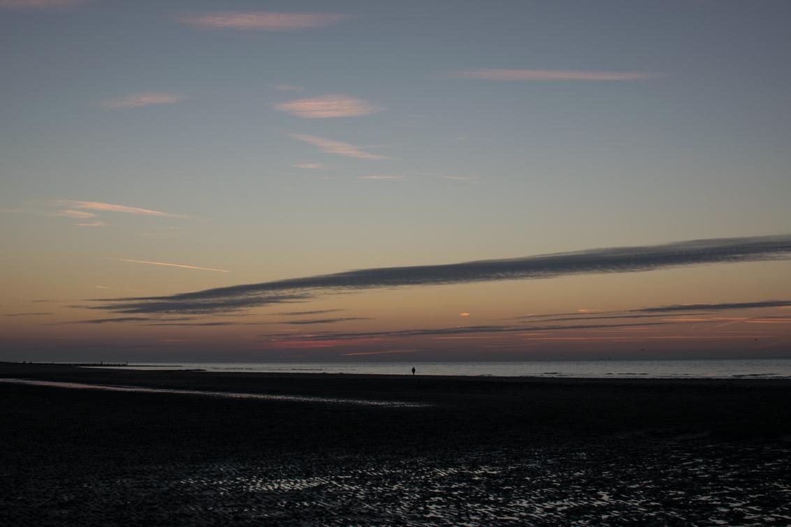 Strand bij Oostkapelle - Eenzame wandelaar op het strand van Oostkapelle net na zonsondergang - foto door jurriaanpoesse op 12-12-2018 - deze foto bevat: lucht, wolken, strand, zee, natuur, licht, herfst, avond, zonsondergang, vakantie, landschap, duinen, zand, eenzaamheid