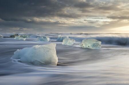 Go with the Flow - Vlak na zonsopkomst op Diamond Beach in IJsland. Door de storm waren er dit keer extreem veel brokken ijs, afkomstig van de nabije gletsjer, op het s - foto door weimaraan op 06-03-2020 - deze foto bevat: lucht, wolken, zon, strand, zee, water, natuur, licht, sneeuw, winter, ijs, landschap, zonsopkomst, zand, ijsland, golven, koud, kust, ijsbergen, lange sluitertijd, ijsblokken, diamond beach