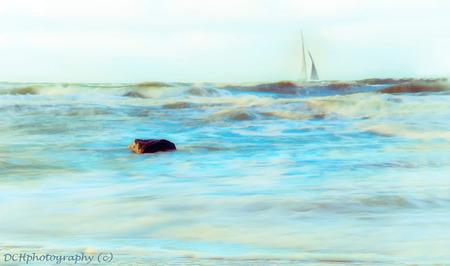 Rots in de branding - Bewerking met nik filters.  Iedereen bedankt voor de fijne reacties bij mijn vorige opname. - foto door Dodsi op 28-11-2017 - deze foto bevat: wolken, strand, zee, water, licht, boot, herfst, zeilboot, bewerkt, landschap, branding, kust, bewerking, nostalgie, rots, photoshop, creatief, textuur, nik, lange sluitertijd