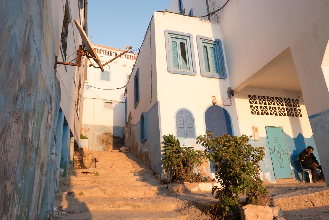 Taghazout - Dutje - Een man doet een dutje in het avondlicht van Tagahzout, Marokko. - foto door Krulkoos op 02-02-2020 - deze foto bevat: kleuren, kleur, straat, zon, avond, zonsondergang, slaap, slapen, marokko, straatbeeld, colour, straatfotografie, break, pauze, dutje, pastel, nap, dutten, pastels, avondfotografie, tukken, colorful, morocco, maroc, maurice weststrate, lx100, taghazout, colors of morocco, pastel colors, napping