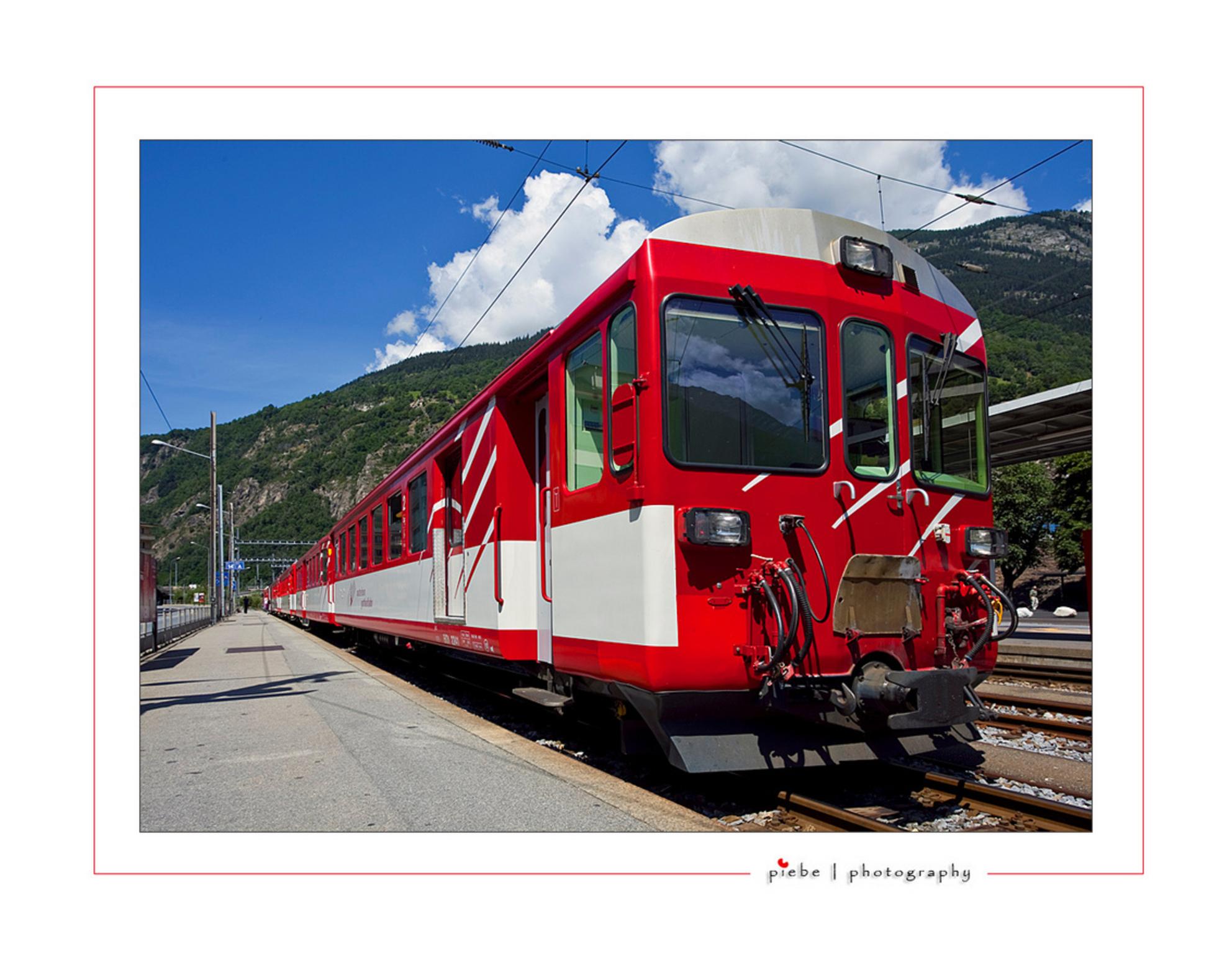 Rode bergtrein - Deze foto is weer vanuit Wallis, Zwitserland. Genomen in Brig bij het station. Ik probeer zoveel mogelijk van de omgeving te laten zien, dus misschie - foto door Piebe op 21-07-2009 - deze foto bevat: station, rood, trein, bergen, zwitserland, wallis, brig - Deze foto mag gebruikt worden in een Zoom.nl publicatie
