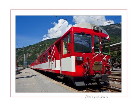 Rode bergtrein - Deze foto is weer vanuit Wallis, Zwitserland. Genomen in Brig bij het station. Ik probeer zoveel mogelijk van de omgeving te laten zien, dus misschie - foto door Piebe op 21-07-2009 - deze foto bevat: station, rood, trein, bergen, zwitserland, wallis, brig