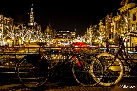 Kerstmarkt Leiden - Vanavond een uurtje gefotografeerd bij de Kerstmarkt in Leiden. Leiden, een studentenstad bij uitstek. Dus ook de zgn studentenfietsen zijn in grote  - foto door mkview op 17-12-2015 - deze foto bevat: oud, kleur, straat, water, licht, kerst, avond, fiets, architectuur, markt, spiegeling, reflectie, kerk, stad, nacht, gracht, leiden, lantaarn, huis, feest, straatfotografie, centrum, lichtjes, evenement, kerstmarkt, straatverlichting, kerstverlichting, kerstversiering, studentenstad