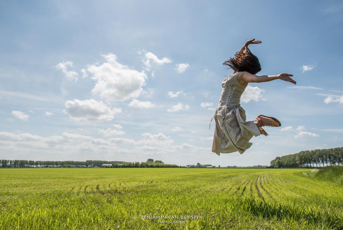 Zeeuws Vlaanderen - Een vrouw springt hoog de lucht in boven het vlakke Zeeuws Vlaamse land. - foto door eachat op 17-05-2015 - deze foto bevat: vrouw, groen, blauw, panorama, platteland, voorjaar, zeeland, nederland, springen, klassiek, braakman, zeeuws vlaanderen