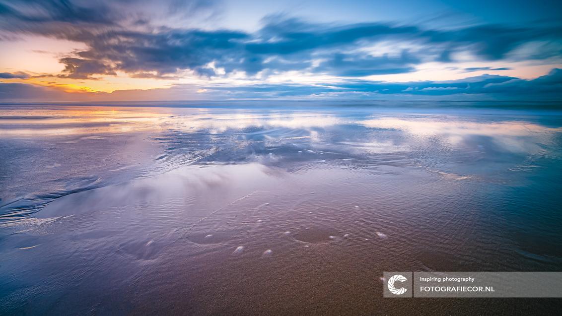Aan de Noordzee - Op dit soort momenten weet ik weer waarom ik zo graag naar de kust ga! - foto door Fotografiecor op 31-01-2021 - deze foto bevat: lucht, wolken, zon, strand, zee, water, panorama, natuur, licht, zonsondergang, vakantie, spiegeling, landschap, tegenlicht, zonsopkomst, zand, kust, lange sluitertijd