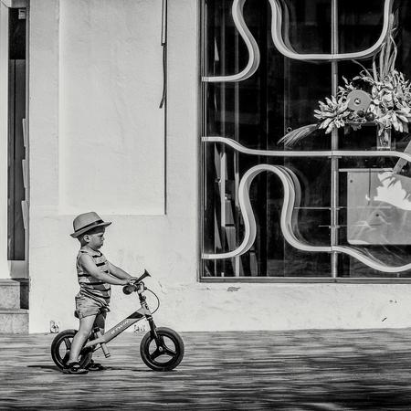 Iedereen klaar... START. - Soms kunnen we wat verbeeldingskracht gebruiken om te ontsnappen aan de dagelijkse stress. Is dit een wedstrijd, wordt ie geroepen door zijn ouders o - foto door RogerHamblok op 10-09-2019 - deze foto bevat: straat, fiets, stad, kind, zwartwit, jongetje, plein, straatfotografie, winkel, loopfiets