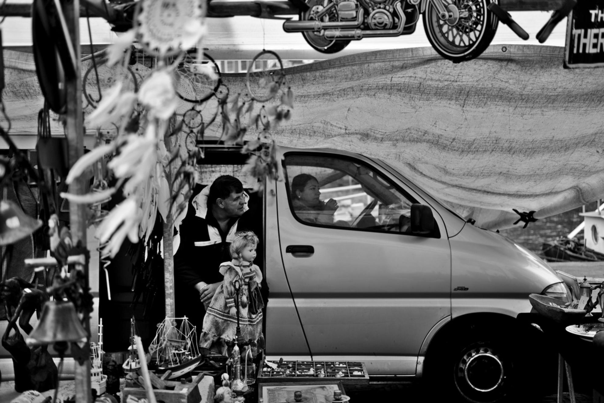 Wachtende - Ik ben net nieuw in Amsterdam en nu al verliefd op de Waterlooplein markt, wat een drukke, dynamische en interessante plek om foto's te maken. Ben he - foto door Casnils op 28-10-2020 - deze foto bevat: oud, man, mensen, amsterdam, straat, markt, auto, zwartwit, plein, straatfotografie, centrum