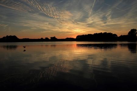 Sunset - Vlakbij de IJssel in Gorssel is een groot zandgat waar het heel stil is 's avonds en waar de zon heel mooi ondergaat. Je voelt dan de rust en stilte. - foto door henk-eilander op 03-10-2013 - deze foto bevat: water, natuur, ijssel, zonsondergang