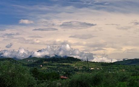 Surrealistische wolken boven bergen naast Gardameer