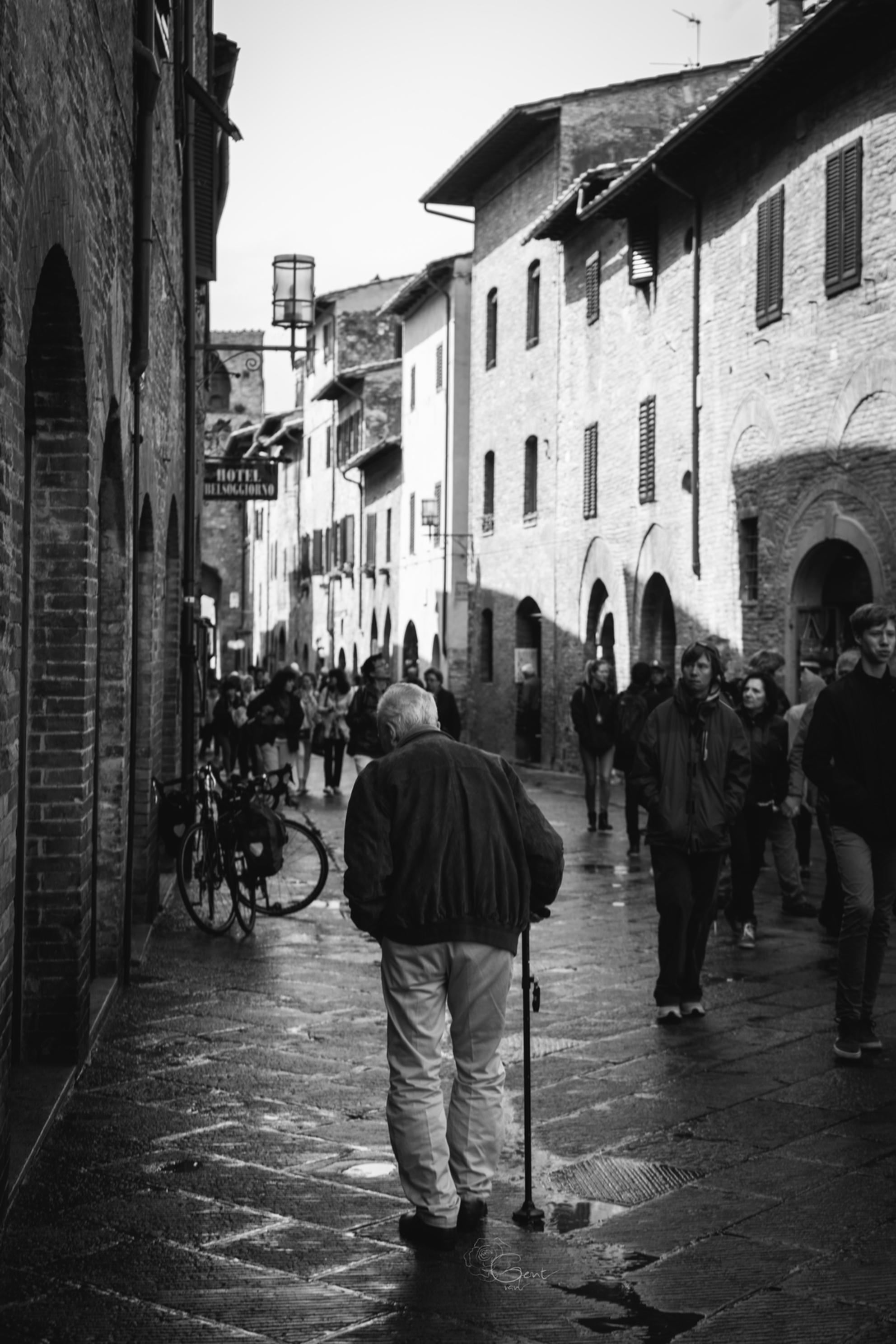 Je eigen weg - Hij was niet zo snel, maar hij ging naar boven. - foto door Roosvangent op 22-01-2017 - deze foto bevat: man, schaduw, zwartwit, toscane, italie, stok, straatje, wandelaar, Oude man - Deze foto mag gebruikt worden in een Zoom.nl publicatie
