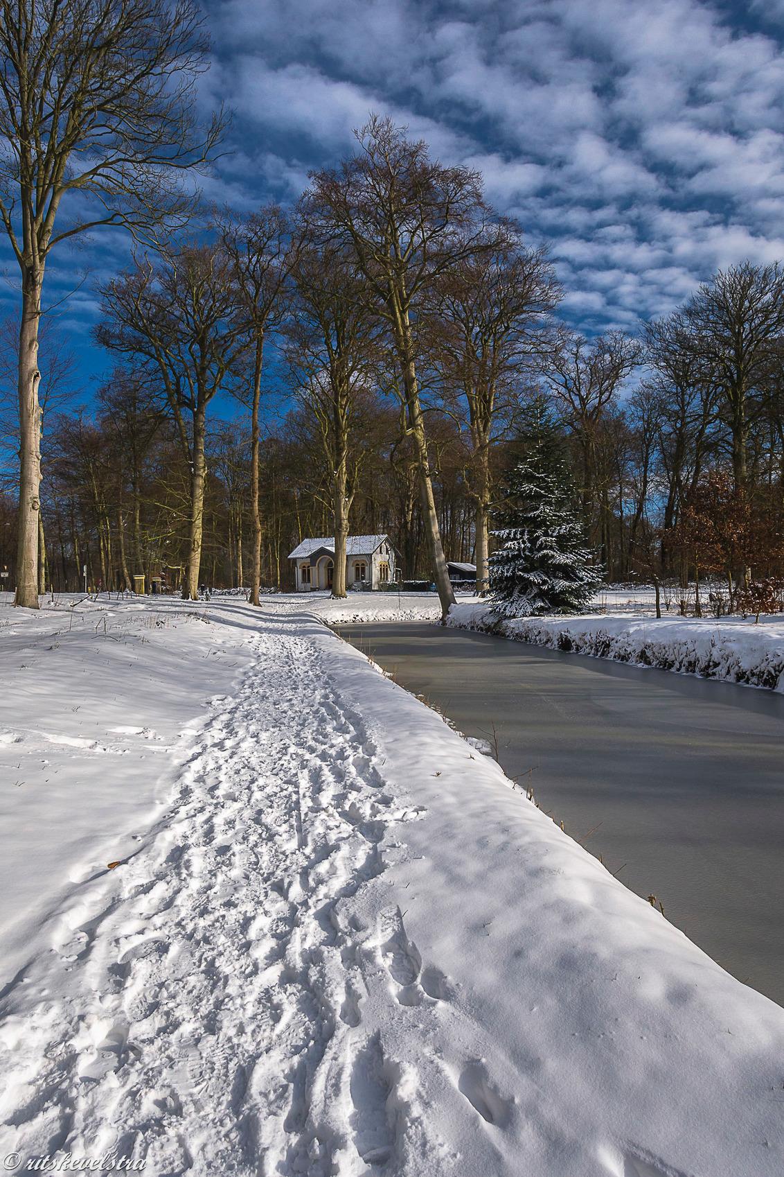 portierswoning Nijenburg - Op de plek van de vorige foto naar links en dan zie over de sneeuw de mooie witte portierswoning van Nijenburg met een blauwe lucht. - foto door rits op 10-02-2021 - deze foto bevat: wolken, sneeuw, natuurmonumenten, nijenburg, heilooerbos