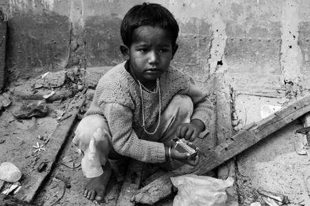 Vuurtje stoken - Een straatkind zit in een oude boot die op de wal ligt met lucifers te spelen.Denk niet dat een groot vuur wordt - foto door dirka op 28-12-2011 - deze foto bevat: vuur, kind, india, straatbeeld, varanasi