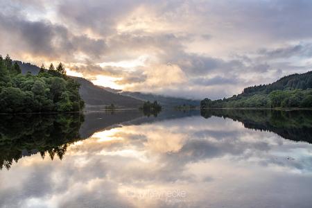 LOCH CHON - Prachtige wolkenpartijen en weerspiegeling tijdens de zonsondergang bij Loch Chon in Schotland. - foto door eddy-reynecke op 02-03-2019 - deze foto bevat: lucht, wolken, water, natuur, licht, avond, zonsondergang, spiegeling, landschap, bos, tegenlicht, bomen, bergen, meer, schotland, lange sluitertijd, loch chon