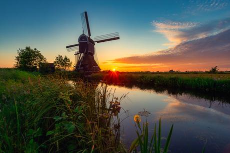 Hollands landschap met zonsondergang