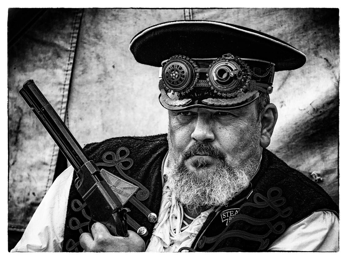 The Steampunk Guv'nor - Midden op het veld tijdens de Fotofair 2018 in Hilvarenbeek was een Steampunk campement, waarbij enthousiate mensen in een roleplay van de steampunk  - foto door Dutchone_zoom op 14-06-2018 - deze foto bevat: man, portret, model, daglicht, ogen, haar, pet, zwartwit, emotie, pistool, fotoshoot, leider, olympus, hilvarenbeek, fictief, acteur, steampunk, om-d, fotofair, e-m10 mk.ii, 2018, roleplay, guv'nor, governor