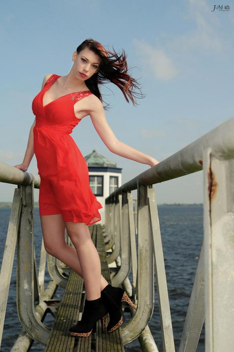 Girl in red dress posing in the wind