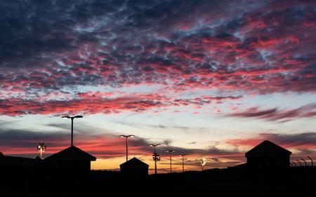 Zonsondergang (Parkeergarage) - Na een filmbezoek aan The Incredibles 2, zag ik een kleurrijke zonsondergang. Ik heb de afleidende lichtjes in de silhouette weg retoucheerd. - foto door Kevin26 op 11-12-2018 - deze foto bevat: lucht, wolken, rood, blauw, natuur, geel, zwart, silhouette, nikon, dak, willemstad, curacao, parkeergarage, lightroom, otrobanda, caraiben, 2018, d5600