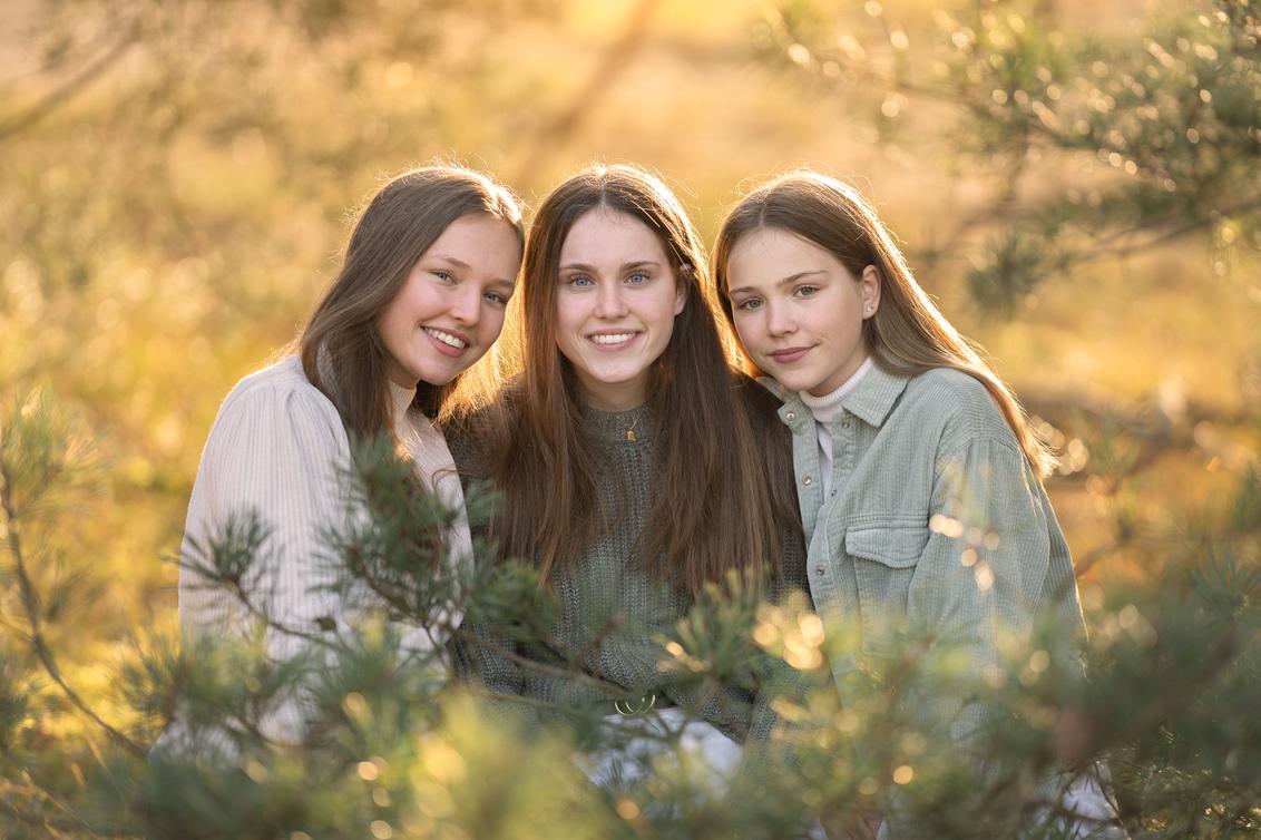 Zusjes - - - foto door BrendaRoos op 08-12-2020 - deze foto bevat: mensen, portret, tegenlicht, daglicht, kind, haar, meisje, lief, familie, groepsportret, fotoshoot, naaldbomen, bokeh